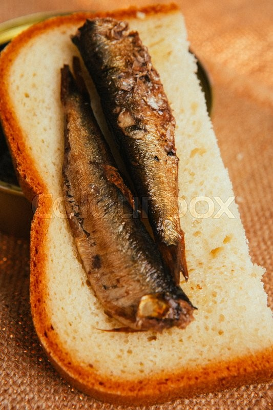 Stock image of 'open can and sandwich with   of sprats on sackcloth background'