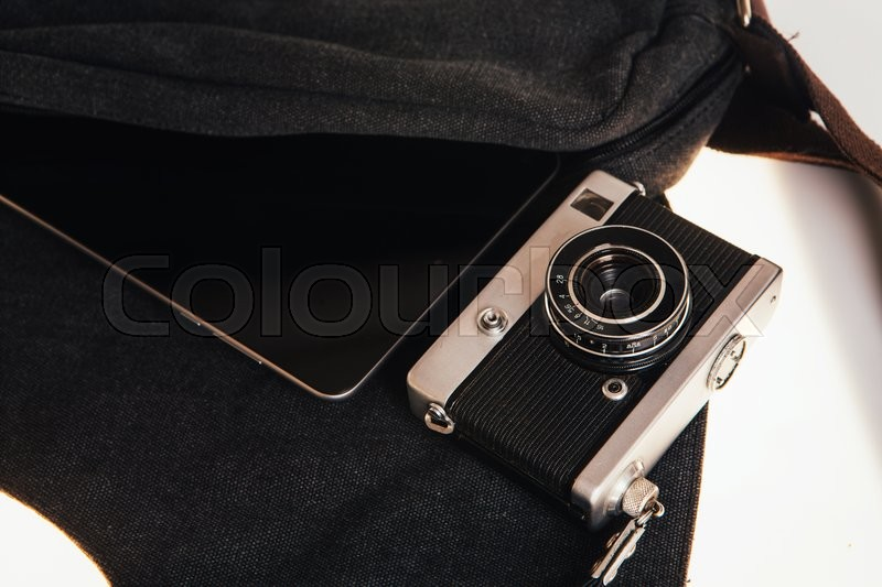 Stock image of 'Vintage camera and tablet computer  on a dark bag'