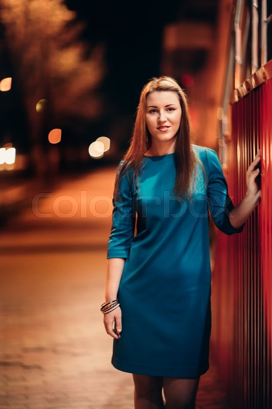Stock image of 'beautiful girl in a blue  dress against the backdrop of the city at night'