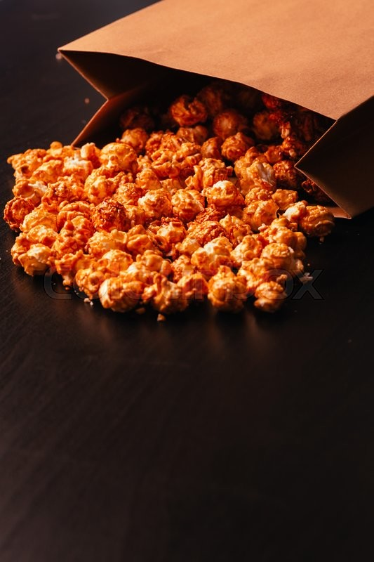 Stock image of 'many popcorn in a paper bag on a dark background'