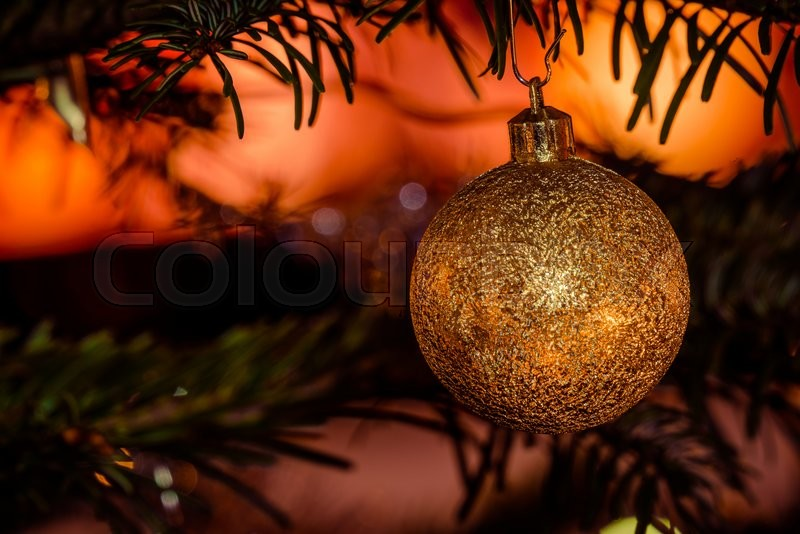 Stock image of 'Golden Christmas bauble on a tree with glittering lights'
