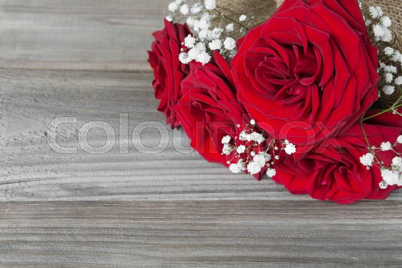 Stock image of 'Lonely bouquet of beautiful red roses lying on the gray background of old wooden boards'