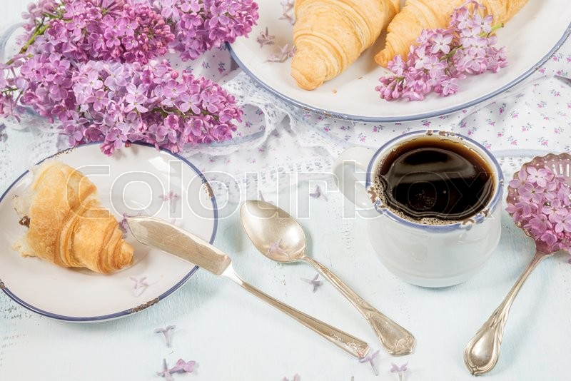 Stock image of 'Spring breakfast with a cup of black coffee, croissants and lilac flowers'
