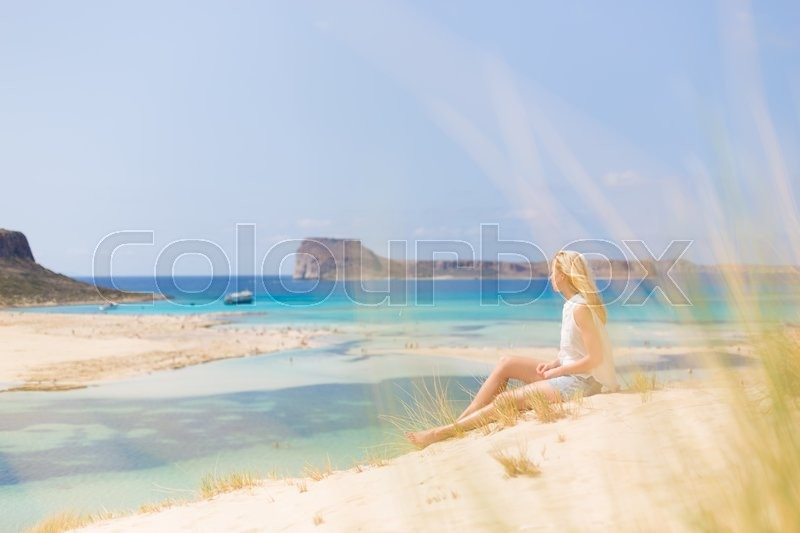 Stock image of 'Relaxed woman enjoying sun, freedom and life an a beautiful sandy beach of Balos in Greece. Young lady feeling free, relaxed and happy. Vacations, freedom, happiness, enjoyment and well being.'