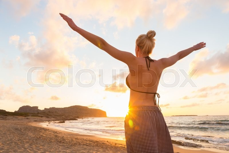 Stock image of 'Relaxed woman, arms rised, enjoying sun, freedom and life an beautiful beach in sunset. Young lady feeling free, relaxed and happy. Concept of vacations, freedom, happiness, enjoyment and well being.'