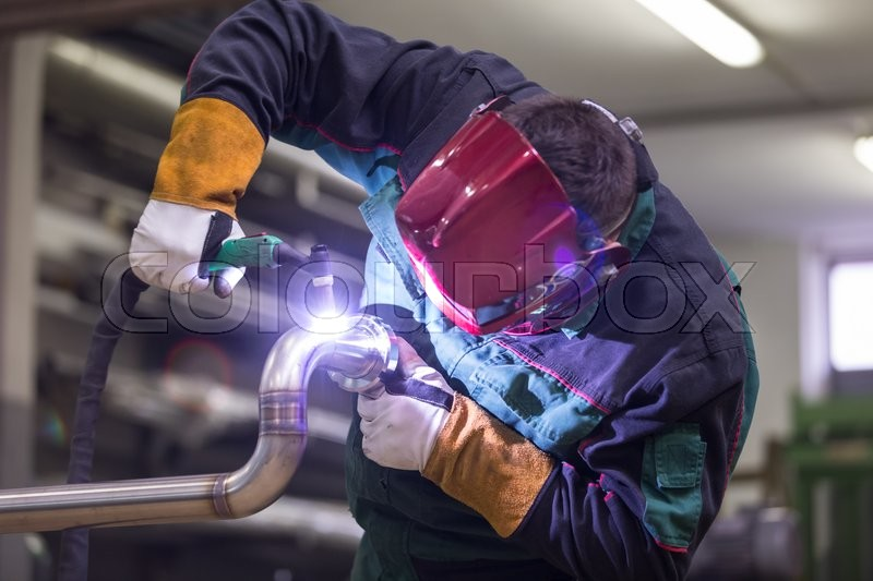 Stock image of 'Industrial worker with protective mask welding inox elements in steel structures manufacture workshop.'
