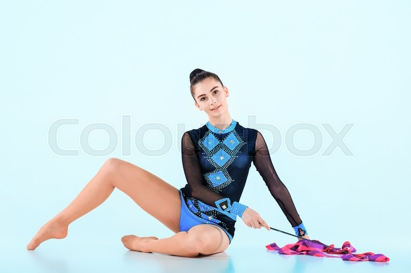 Stock image of 'The girl doing gymnastics dance with colored ribbon on a blue background'