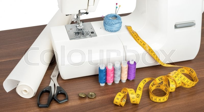 Stock image of 'Sewing machine with accessories on wood table'