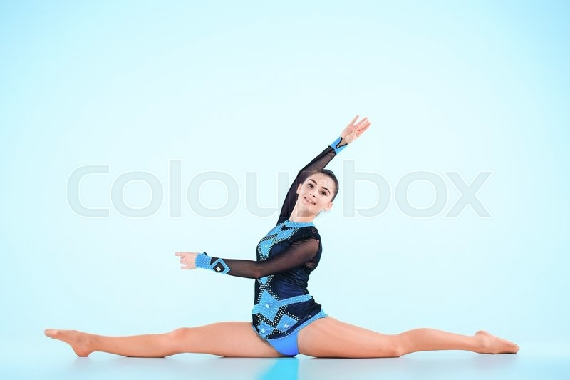 Stock image of 'The girl doing gymnastics dance on a blue background'