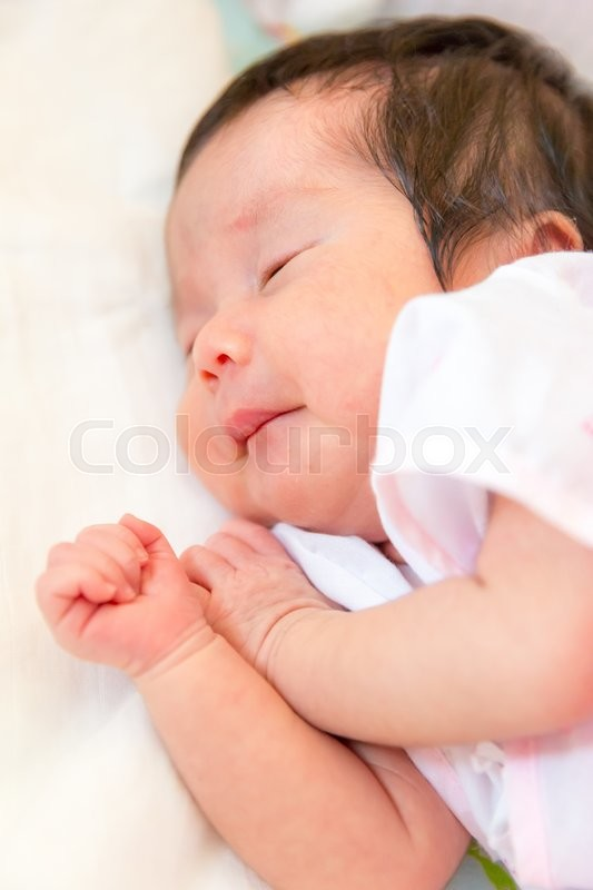 Stock image of 'Peaceful sleeping baby lying on a bed'
