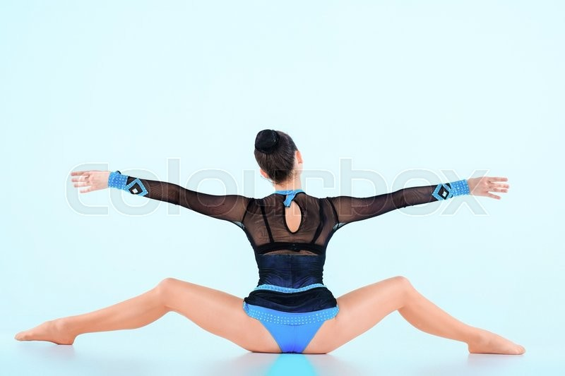 Stock image of 'The back view of girl, doing gymnastics dance on blue background'