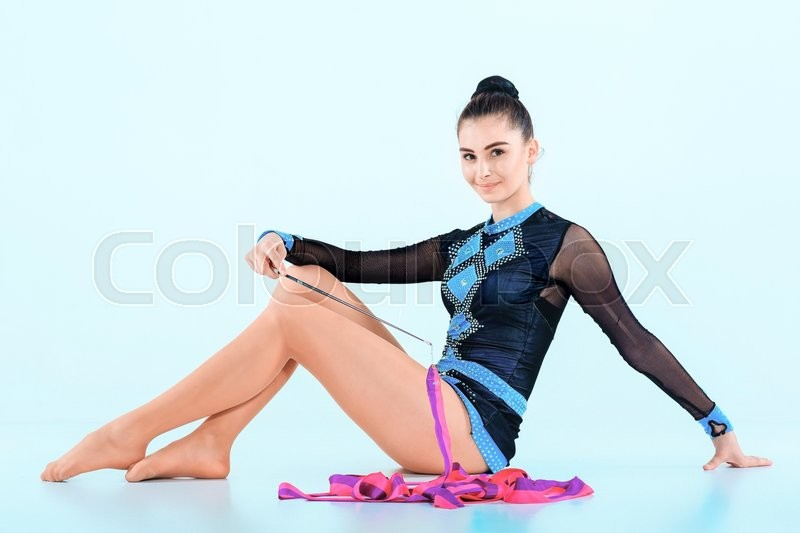 Stock image of 'The girl sitting with colored ribbon on a blue background'