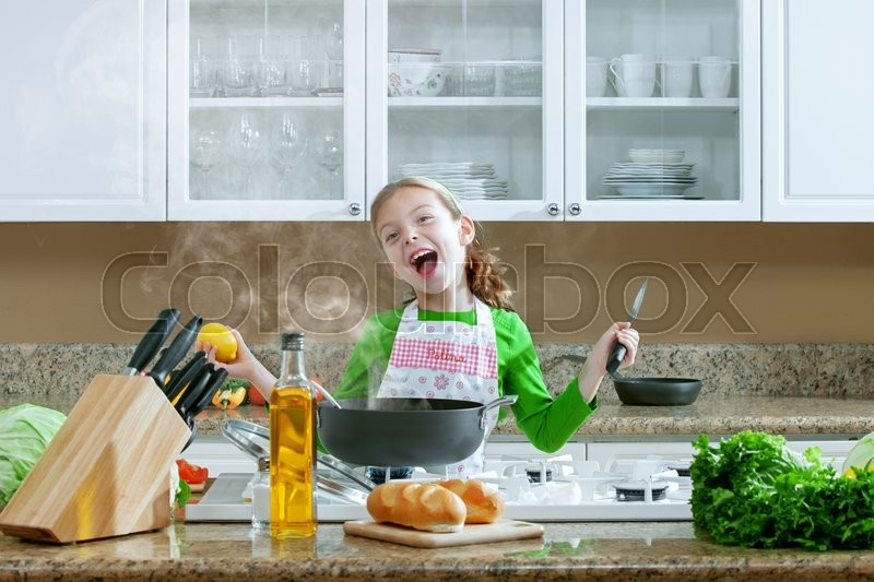 Stock image of 'view of young beautiful girl cooking at the kitchen'