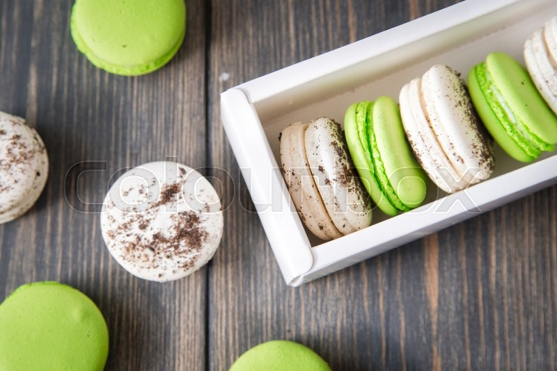 Stock image of 'Colorful sweet macaroons on vintage wooden background.'