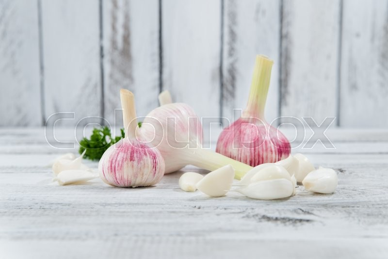 Stock image of 'peeled garlic on vintage wooden background, close-up shot'