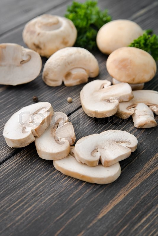 Stock image of 'White mushrooms champignons, old wooden table, rustic style, selective focus'