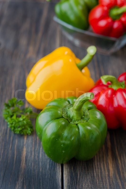 Stock image of 'Assorted colorful varieties of sweet peppers sitting on old wooden  table, rustic style, selective focus'