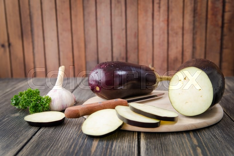 Stock image of 'Fresh healthy eggplants on dark wooden background. '