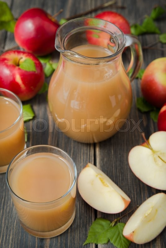 Stock image of 'apple juice on wooden table close up'