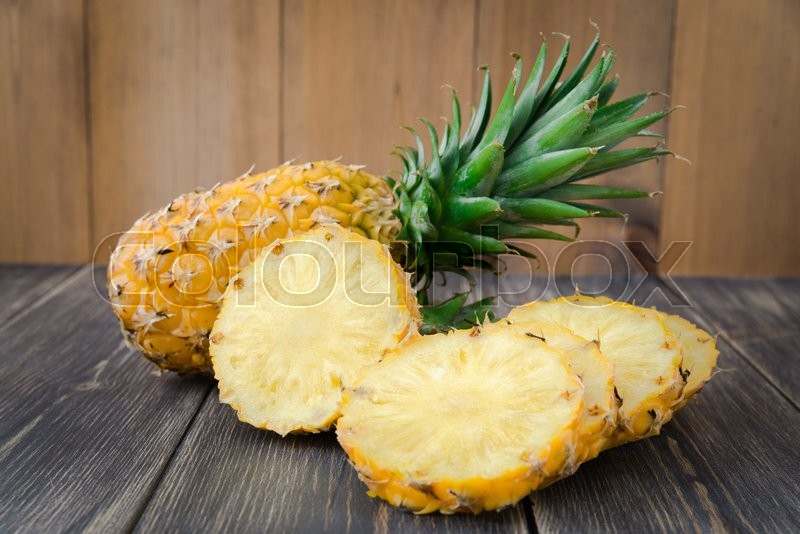 Stock image of 'Fresh organic pineapple on a wooden rustic table'