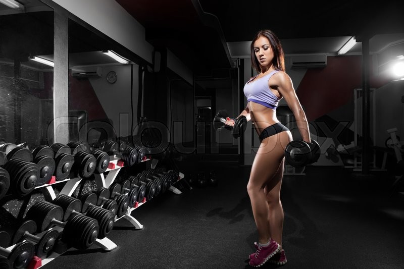 Beautiful sexy girl with perfect abdominal muscles at the gym. The concept of a healthy lifestyle and exercise. Strong woman. Feminism, stock photo