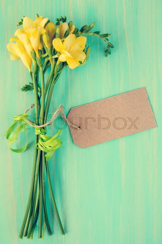 Stock image of 'Yellow freesia flowers with blank tag tied with string'