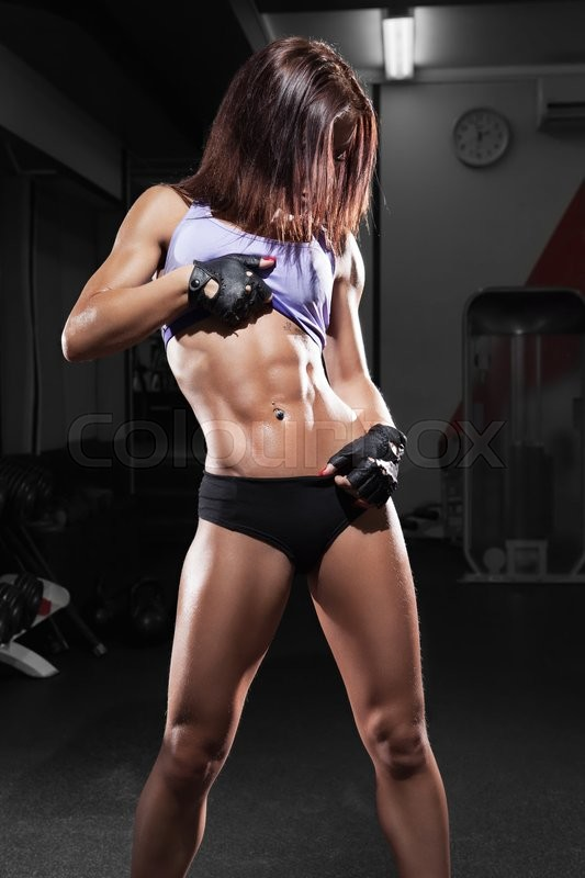 Stock image of 'Beautiful sexy girl with perfect abdominal muscles at the gym. The concept of a healthy lifestyle and exercise. Strong woman. Feminism.'