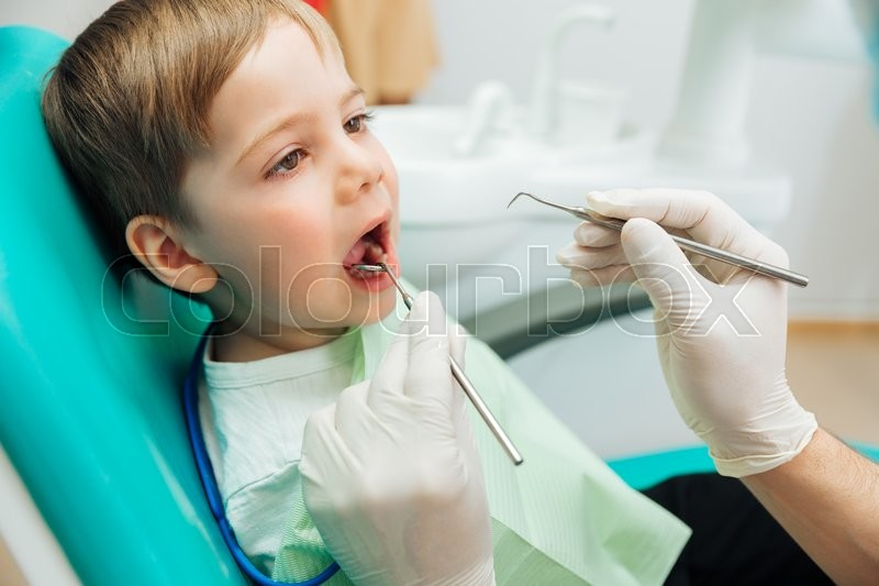 Stock image of 'Cute little boy sitting with mouth opened during oral checkup at the dentist'