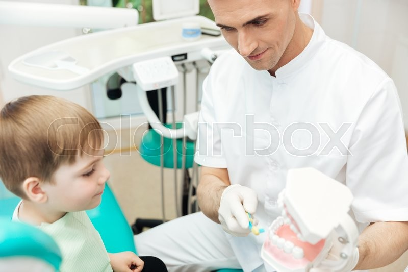 Stock image of 'Handsome man dentist teaching and showing how to brush teeth to cute little boy'