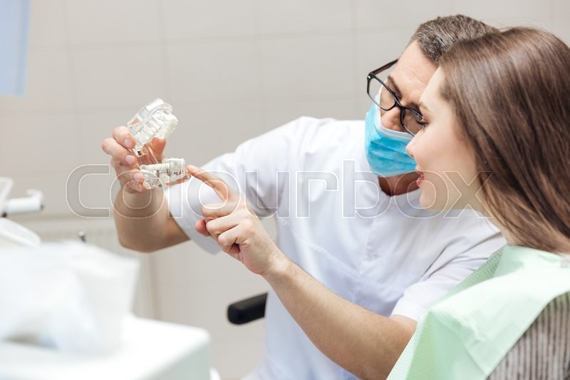 Stock image of 'Man dentist show dentures teeth at dental surgery to his patient at the clinic'
