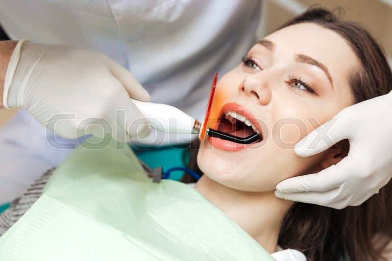 Stock image of 'Close-up portrait of a girl getting her teeth bleached in clinic'
