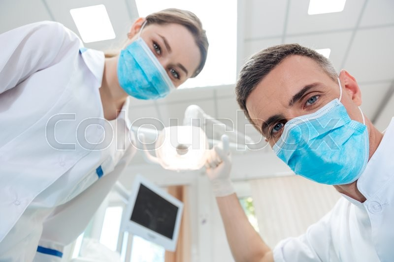 Two dentists making dental treatment to a patient in clinic, stock photo
