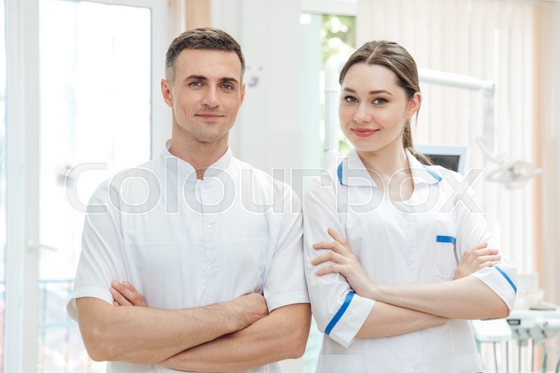 Stock image of 'Portrait of a confident male and female dentists smiling at dental clinic looking at camera'