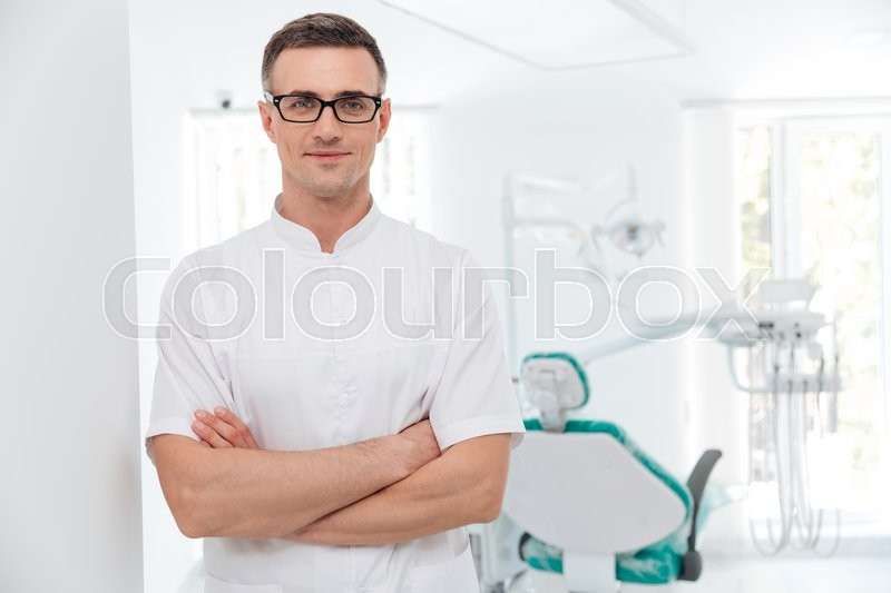 Stock image of 'Female dentist standing with his hands crossed and looking at camera'
