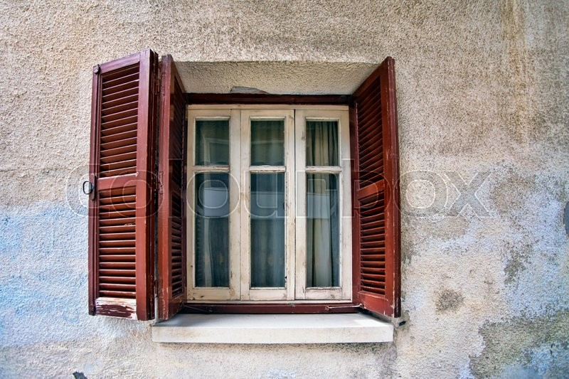 Stock image of 'Old wooden window on stone wall'