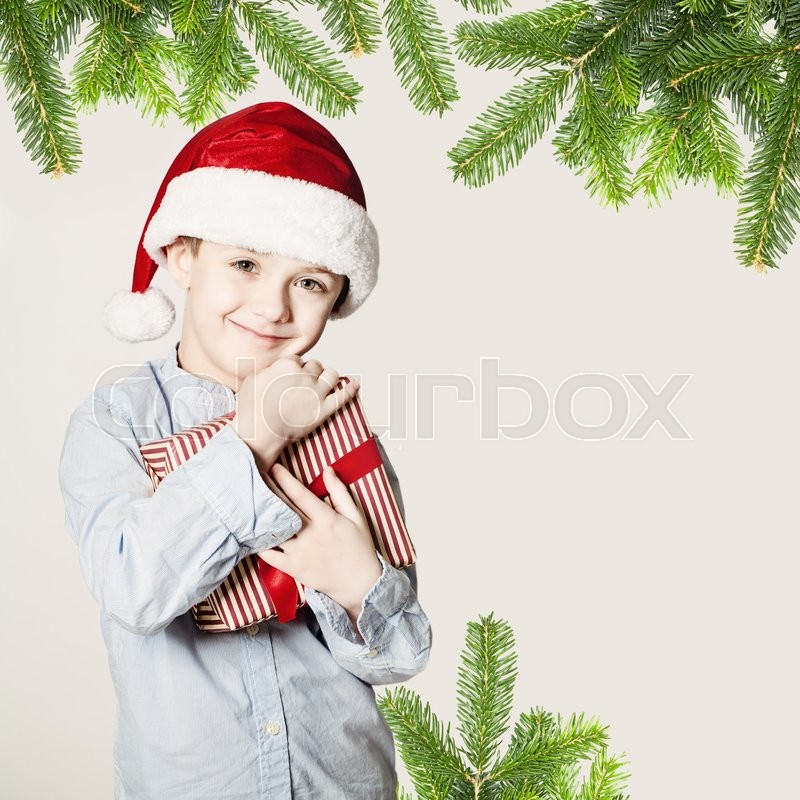 Stock image of 'Small Boy Holding Christmas Gift'