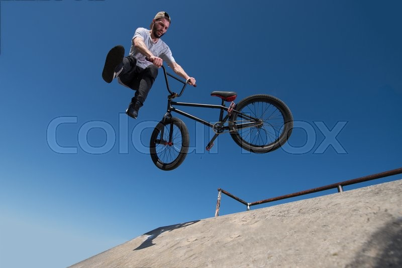 Stock image of 'Bmx rider performing a tail whip at a quarter pipe ramp on a skatepark.'