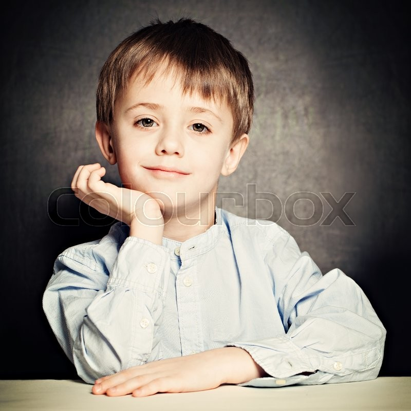 Stock image of 'Cute Little Boy. Happy Child on Blackboard Background'