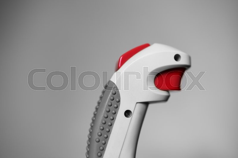 Stock image of 'Retro arcade joystick with red button bokeh background'