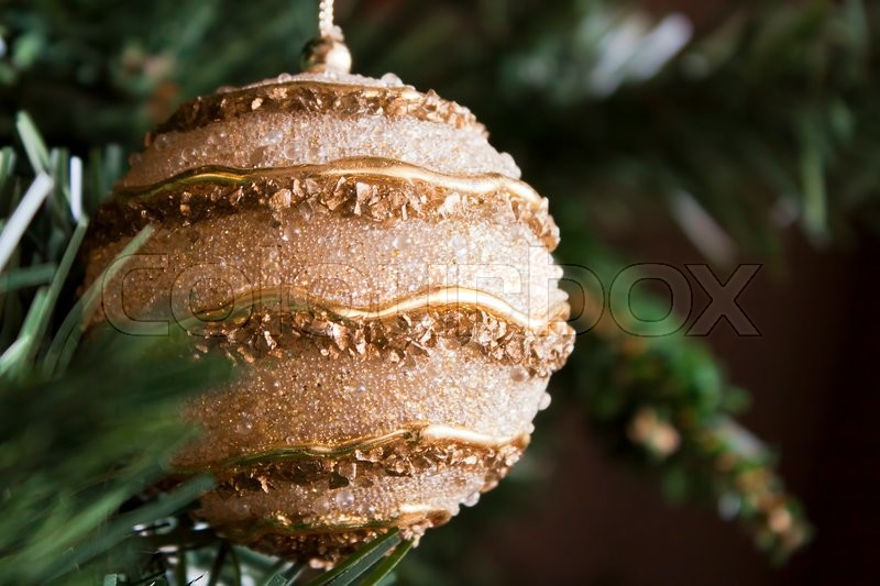 Stock image of 'Glossy golden Christmas ball hanging in the tree as ornament.'
