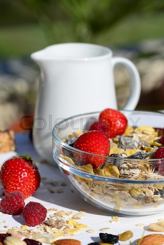 Stock image of 'A delicious and healthy breakfast in the garden of muesli with milk, nuts, berries'