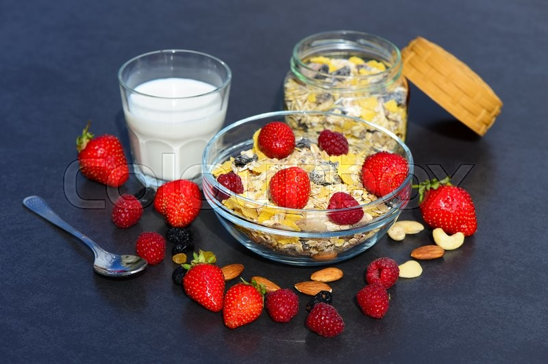 Stock image of 'Muesli with milk, nuts and berries for breakfast diet on a dark background'