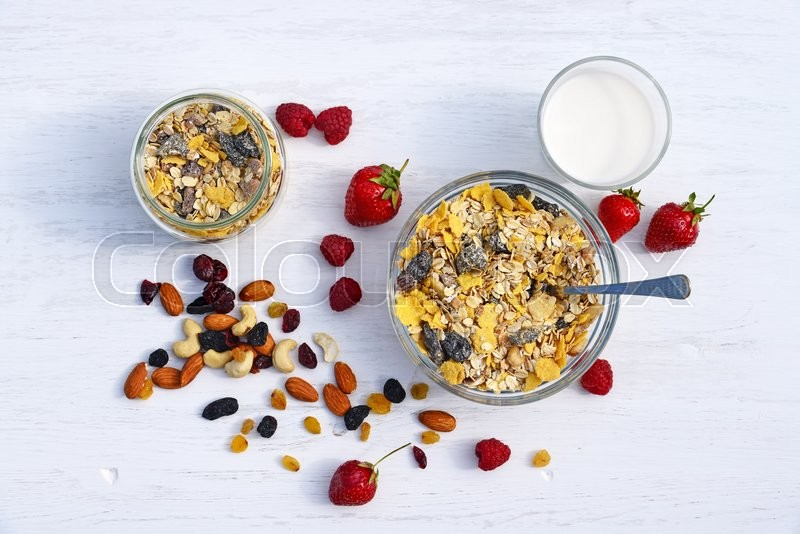 Stock image of 'A healthy breakfast with cereal muesli, milk, nuts and berries'