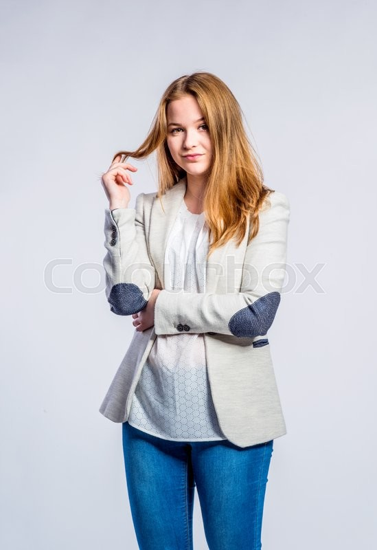 Stock image of 'Teenage girl in jeans and beige jacket, young woman holding hair, studio shot on gray background'