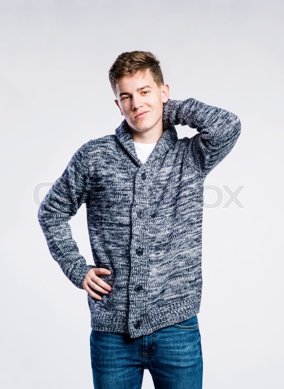Stock image of 'Teenage boy in jeans and dark gray sweater, young man, scratching neck, studio shot on gray background'
