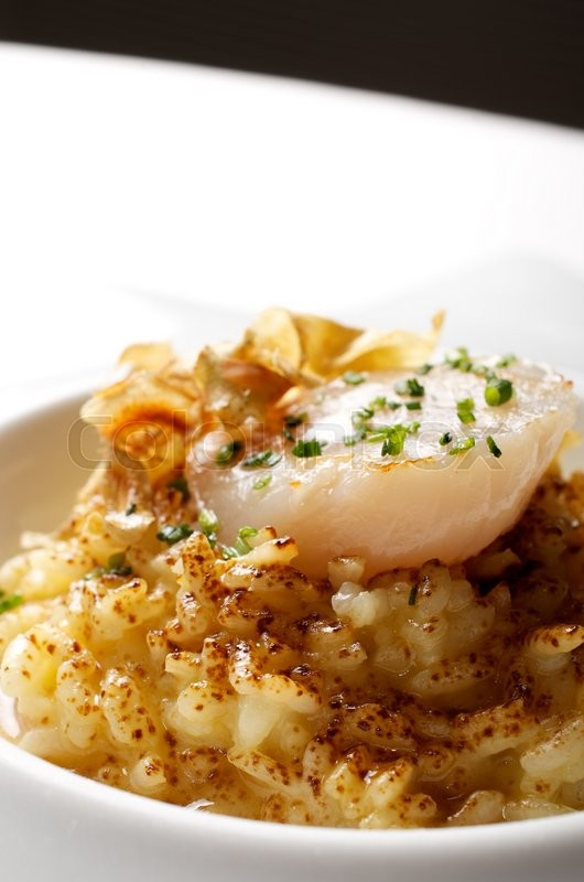 Stock image of 'closeup of a cooked dish of saffron risotto and scallop'