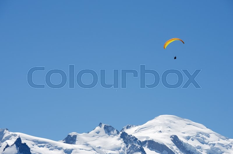 Stock image of 'Paragliding flying over Mont Blanc Massif, in the background is Mont Blanc peak, Alps, Chamonix, France'