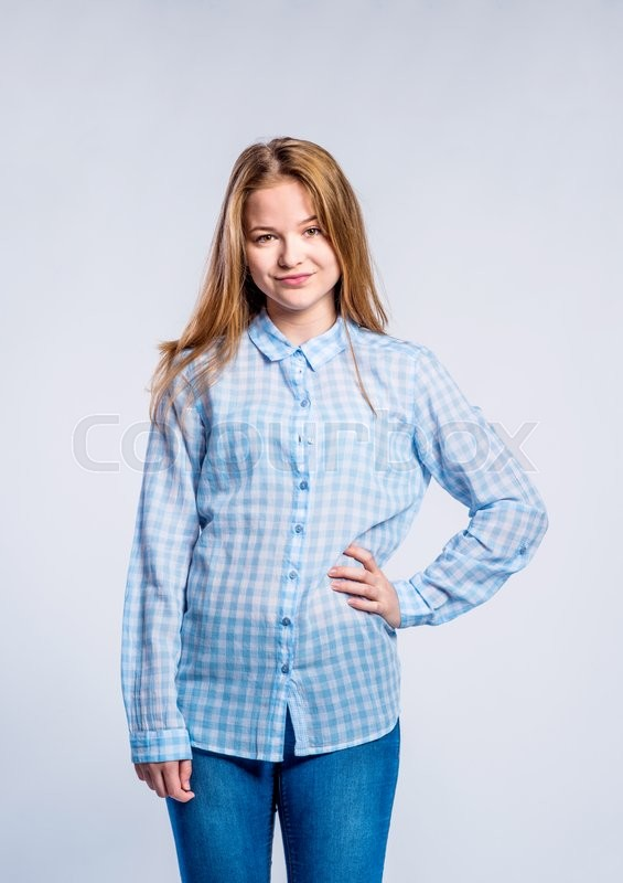 Stock image of 'Teenage girl in jeans and blue checked shirt, young woman, hand on hip, studio shot on gray background'