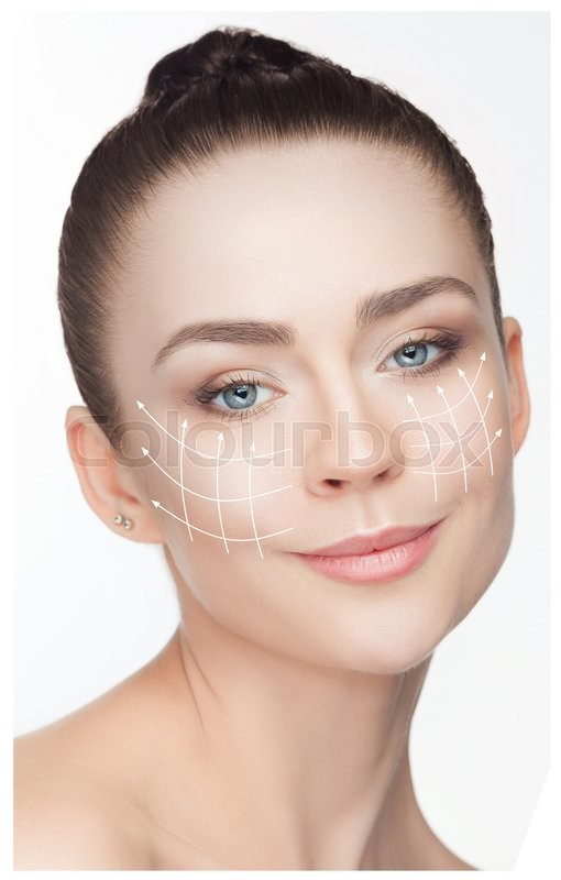 Stock image of 'Beautiful young woman with arrows on face. Plastic surgery concept'