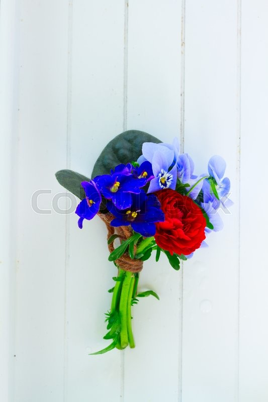 Stock image of 'Posy of violets, pansies and ranunculus on white wooden planks background'